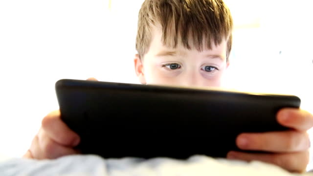 little boy playing on tablet in bed - boys stock videos & royalty-free footage