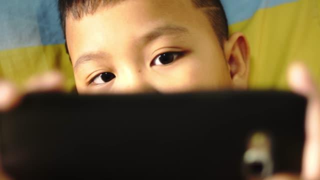 cu: ベッドでタブレットで遊ぶ少年 - 自閉症点の映像素材/bロール