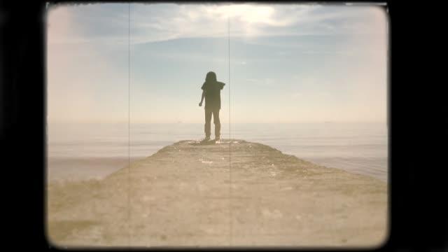 vídeos de stock e filmes b-roll de little boy playing on the beach. 8mm footage. - nostalgia