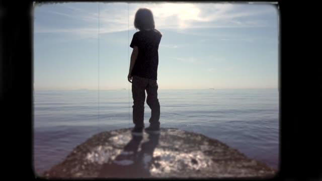 stockvideo's en b-roll-footage met kleine jongen spelen op het strand. 8mm beeldmateriaal. - image