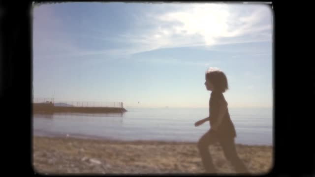 little boy playing on the beach. 8mm footage. - archival stock videos & royalty-free footage