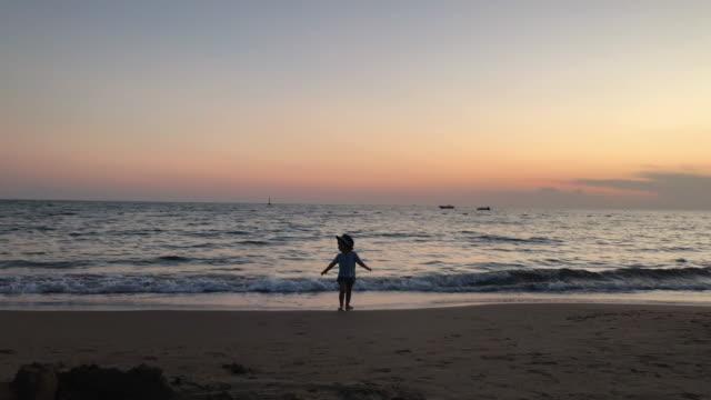 liten pojke leker på stranden i sommarsolnedgång - endast en pojkbaby bildbanksvideor och videomaterial från bakom kulisserna