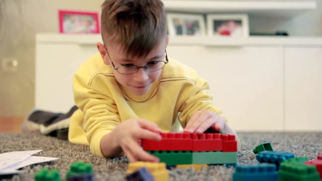 Little boy playing on the livingroom floor with blocks set