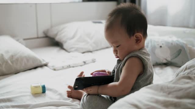 vídeos de stock, filmes e b-roll de garotinho jogando telefone inteligente - 6 11 months