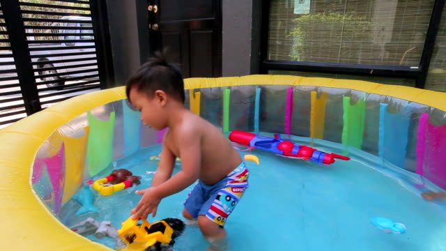 little boy playing toy in inflatable pool - inflatable stock videos & royalty-free footage