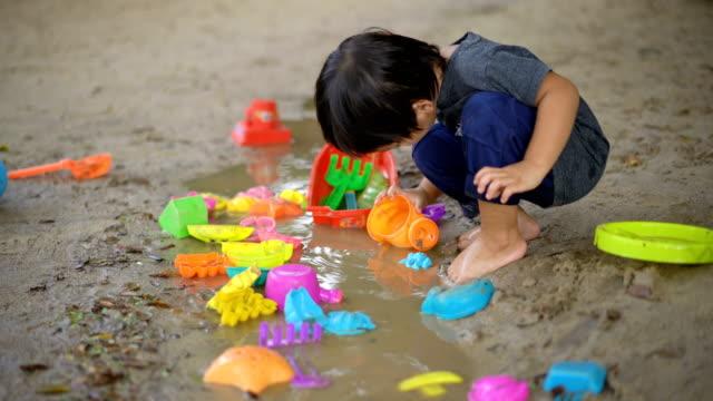 少年は泥の水たまりでおもちゃを演奏します。 - ヨゴレ点の映像素材/bロール