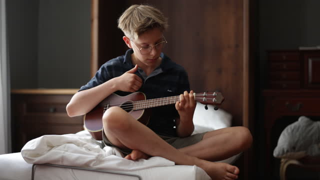 vídeos de stock, filmes e b-roll de garotinho jogando ukulele em casa - ukulele
