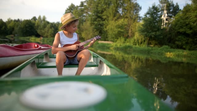 vídeos de stock, filmes e b-roll de menino que joga o ukulele que senta-se na canoa - ukulele