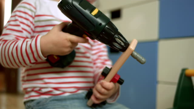 Little Boy Playing With A Drill Toy