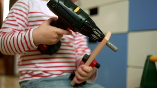 Kleiner Junge spielt mit einem Bohrer-Spielzeug