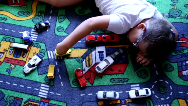 little boy playing with cars look from above - laziness stock videos and b-roll footage