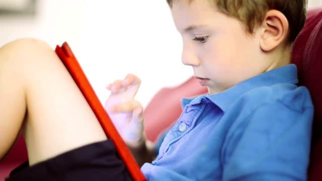 vídeos y material grabado en eventos de stock de poco niño jugando con tableta digital - nativo digital