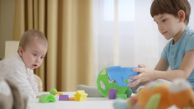 彼の赤ん坊の弟と遊ぶ少年 - 兄弟点の映像素材/bロール