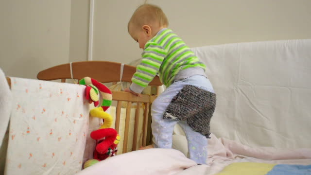 Little boy playing with his cot