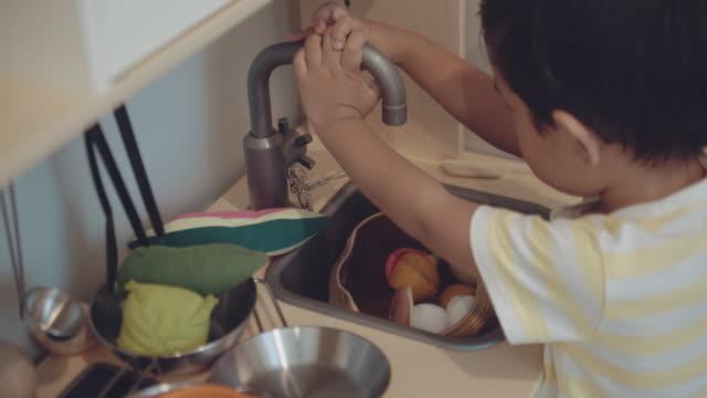 Kleine jongen spelen met keuken stuk speelgoed thuis.