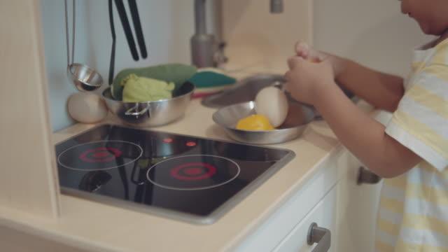 家でキッチンのおもちゃで遊んでいる小さな男の子。 - くつろぐ点の映像素材/bロール