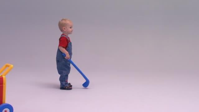 little boy playing with plastic golf set - 全身点の映像素材/bロール