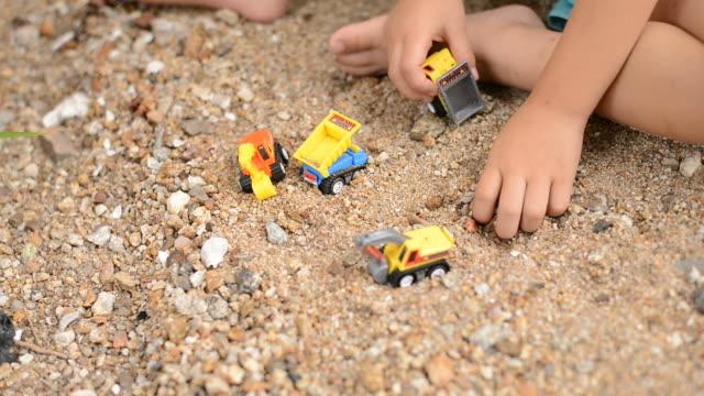 kleiner junge spielt mit plastikspielzeugbagger am sandstrand - traktor stock-videos und b-roll-filmmaterial