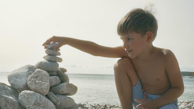 kleine jungen spielen mit steinen am strand in der sonne - nackter oberkörper stock-videos und b-roll-filmmaterial