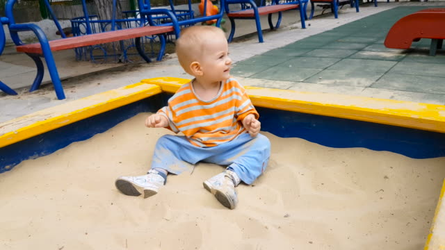 little boy playing with sand crawling in the sandbox - sand pit stock videos and b-roll footage