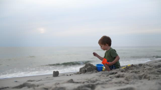 vídeos de stock, filmes e b-roll de menino que joga com o castelo de areia na praia no verão - castelo