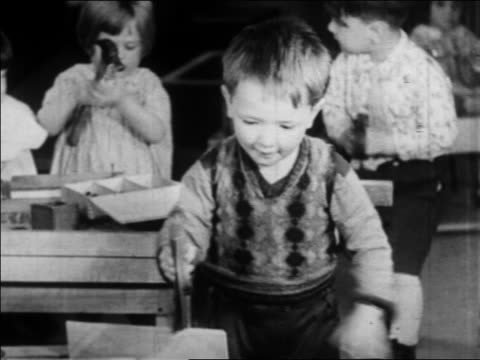 b/w 1934 little boy playing with saw in nursery school / wpa project / newsreel - anno 1934 video stock e b–roll