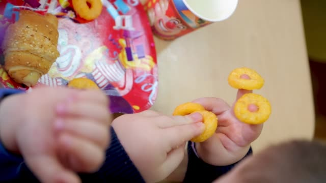 little boy playing with snacks on birthday party while sitting at the table - 4 5 anni video stock e b–roll