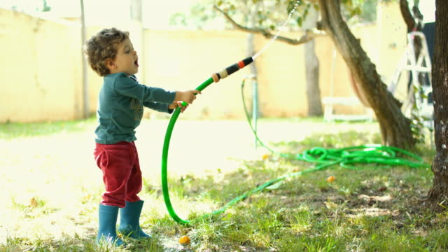little boy playing with the hose and the water in the garden house - ein junge in gummistiefel stock-videos und b-roll-filmmaterial
