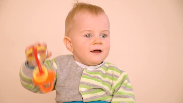 Little boy playing with toy rattle