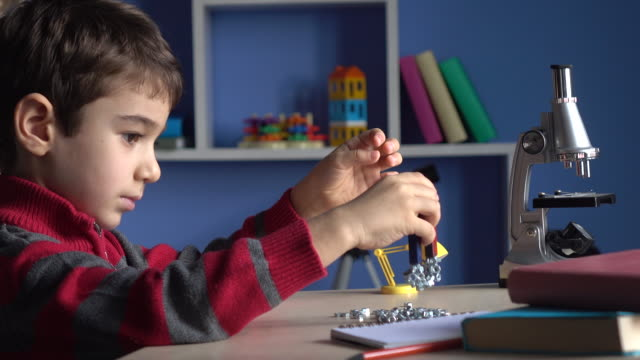 Little Boy Playing With U Magnets In His Room
