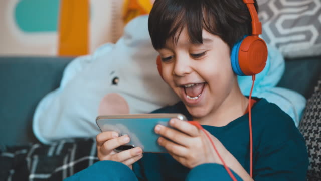 little boy plays mobile games. happily playing games with his phone. he uses headphones to avoid being disturbed. five year old boy playing video game on mobile phone. preschooler plays game on gadget. - contestant stock videos & royalty-free footage