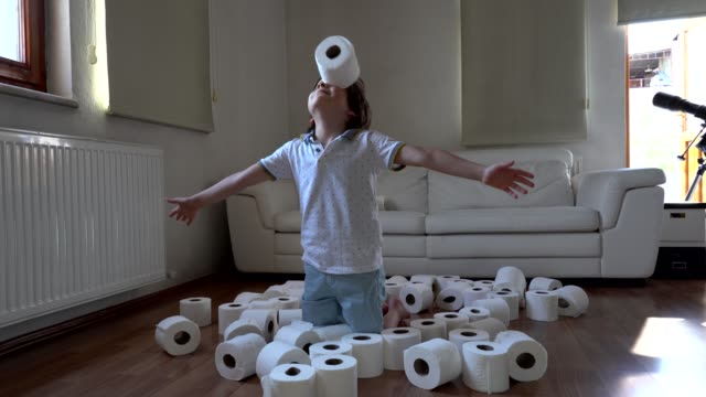 little boy plays with toilet papers when she is bored at home during pandemic - tessuto umano video stock e b–roll