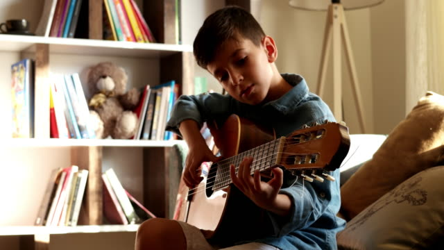 little boy practicing guitar. - plucking an instrument stock videos and b-roll footage