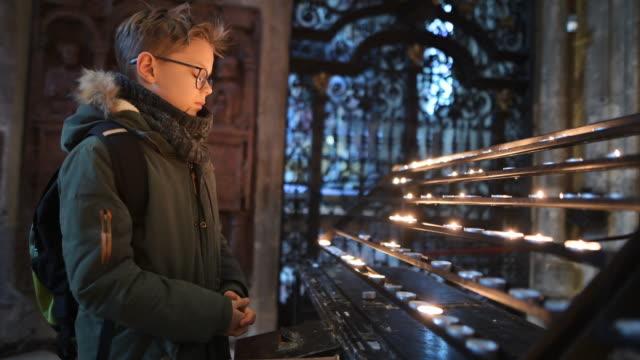 kleiner junge betet in der kirche candelabrum - christentum stock-videos und b-roll-filmmaterial
