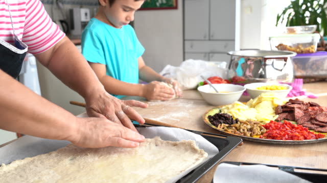 little boy preparing pizza together with his grandmother in kitchen - recipe stock videos & royalty-free footage
