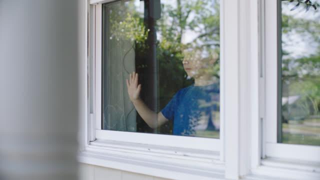 slo mo. little boy presses his hand agaist glass window. - peeking stock videos & royalty-free footage