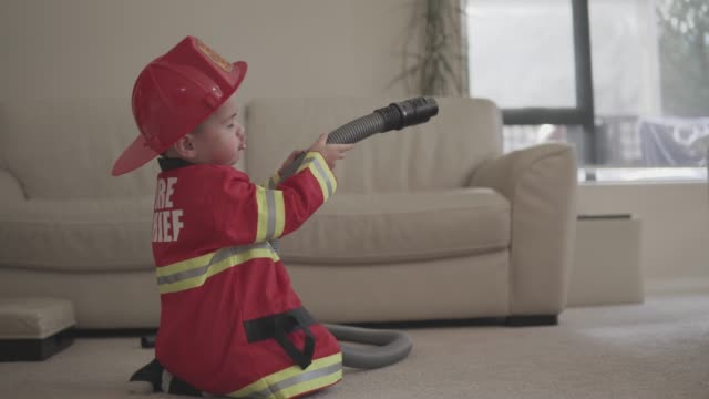 vídeos de stock e filmes b-roll de little boy pretending to be a fireman - bombeiro