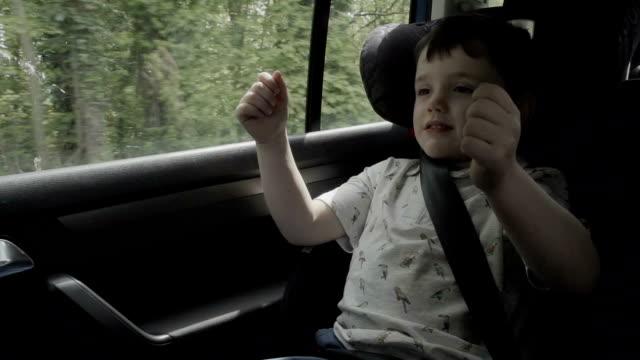 stockvideo's en b-roll-footage met little boy pretending to drive a car - veiligheidsgordel