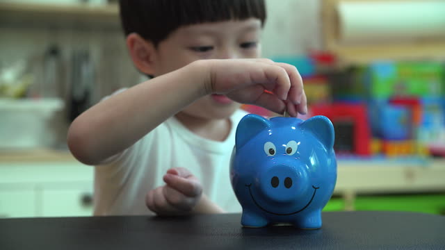 Little boy putting a coin into a piggy bank - kid saving money for future concept