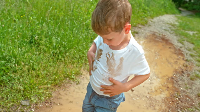 slo mo little boy putting his hands in the muddy puddle and wiping them in his clean white t shirt - all shirts stock videos & royalty-free footage