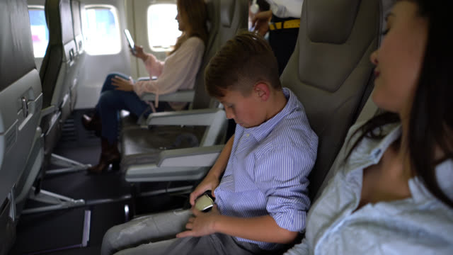 little boy putting on safety seat belt in airplane and air stewardess checking while lovingly touching him on head - crew stock videos & royalty-free footage