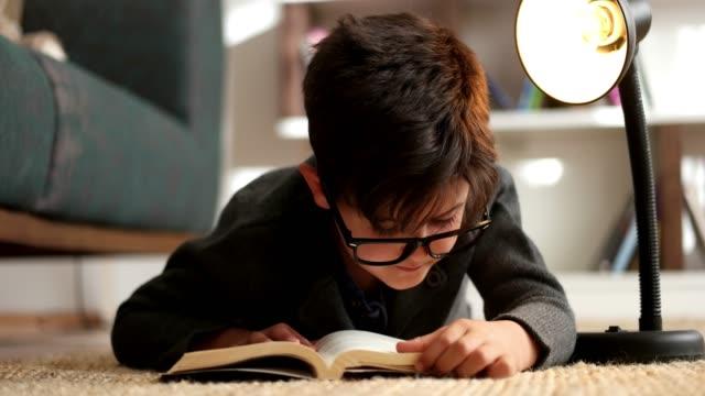 vidéos et rushes de petit garçon lisant un livre sur un tapis - brightly lit