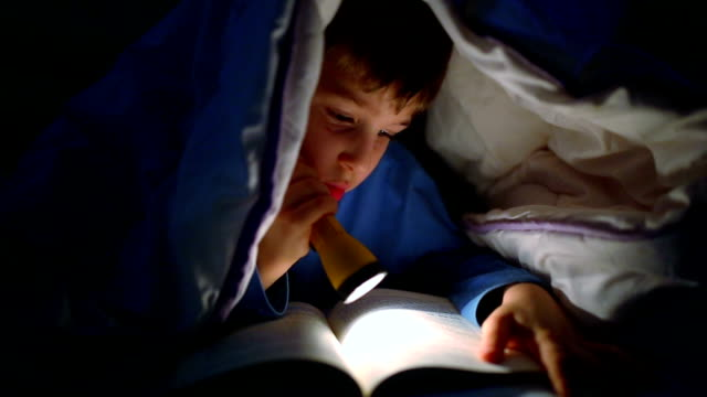 vídeos de stock e filmes b-roll de little boy reading a book under the covers with flashlight - cama
