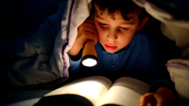 little boy reading a book under the covers with flashlight - children only stock videos & royalty-free footage