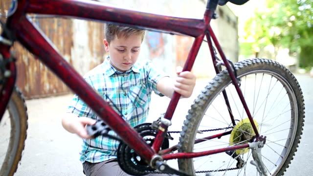 Kleine Junge reparieren ein Fahrrad