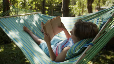 little boy resting on hammock and reading a book - lying down stock videos & royalty-free footage