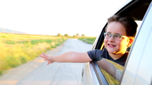 Kleiner Junge fährt in einem Auto aus dem Fenster gelehnt