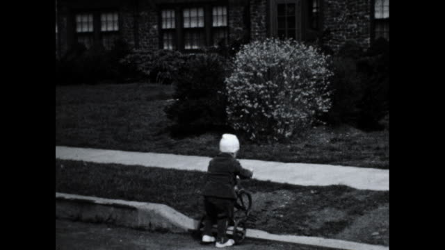 little boy riding a tricycle across the street onto the sidewalk; house in the background - tricycle stock videos & royalty-free footage