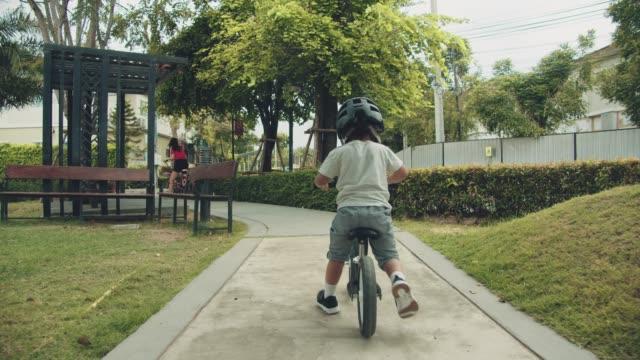 vídeos de stock, filmes e b-roll de bicicletas da equitação do rapaz pequeno - parque público