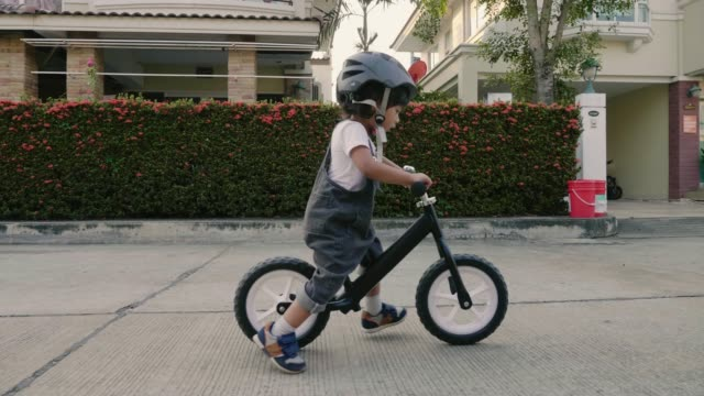 little boy riding her bike outside on a sunny day near the home, thailand - baby boys stock videos & royalty-free footage